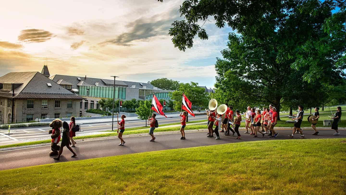 Students in the Big Red Band march past Klarman Hall